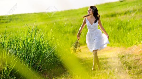 8726304-Candid-skipping-carefree-adorable-woman-in-field-with-flowers-at-summer-sunset--Stock-Photo